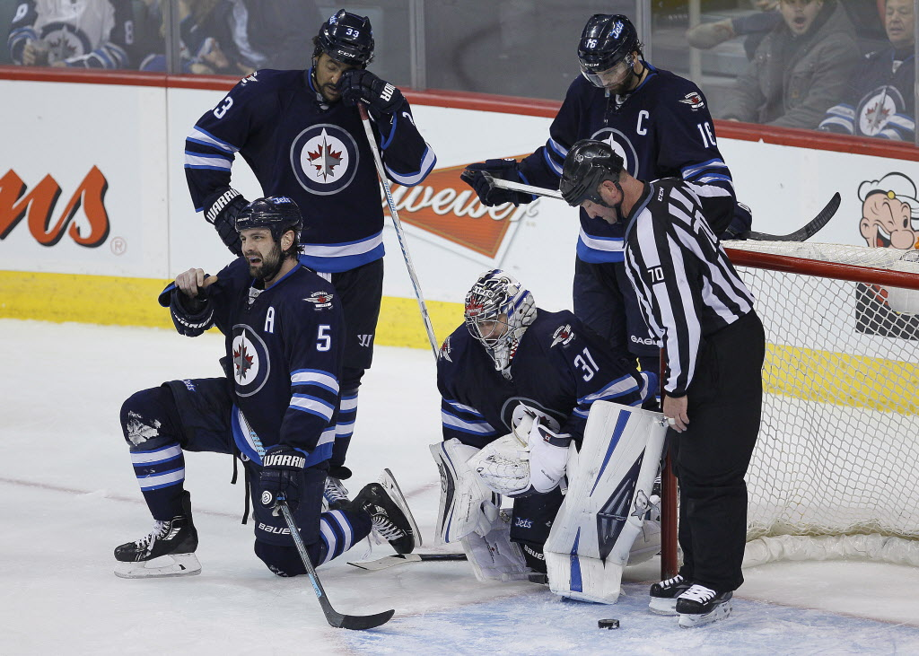 Winnipeg Jets' Mark Stuart (5), Dustin Byfuglien (33), goaltender Ondrej Pavelec (31), and Andrew Ladd (16) react after the Los Angeles Kings score on them during third period. The goal was reviewed and called off.