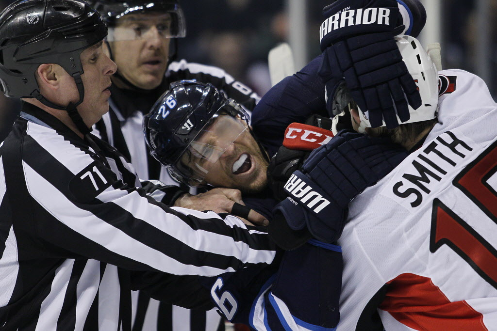 Referees attempt to pull apart Winnipeg Jets' Blake Wheeler (26) and Ottawa Senators' Zack Smith (15) during second period NHL action in Winnipeg on Saturday, March 8, 2014.  (John Woods / THE CANADIAN PRESS)