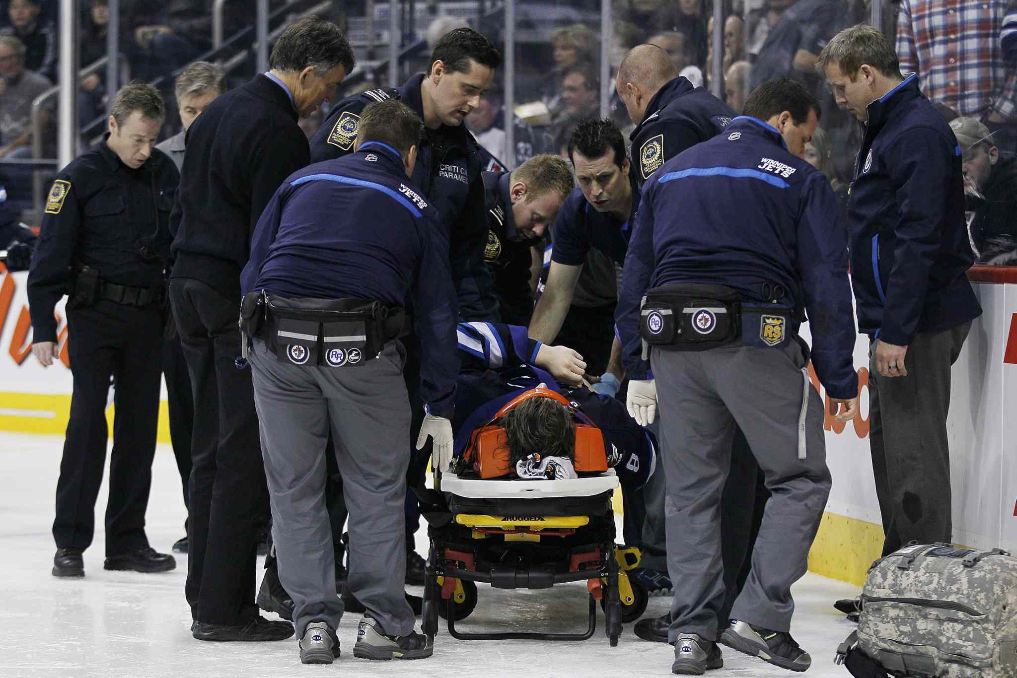 Winnipeg Jets' Jacob Trouba (8) is attended to by paramedics after crashing head first into the boards during second period NHL action against the St. Louis Blues in Winnipeg on Friday, October 18, 2013. THE CANADIAN PRESS/John Woods