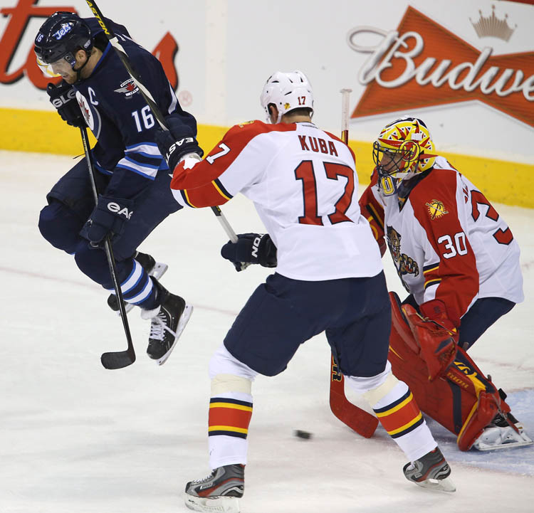 Winnipeg Jets' Andrew Ladd jumps over a shot by Mark Stuart that beat Florida Panthers' goaltender Scott Clemmensen during the second period at MTS Centre Tuesday night. (CP)