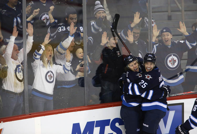 Winnipeg Jets' Bryan Little (18) and Zach Redmond (25) celebrate after the pair combined for Little's game winning goal against the Florida Panthers during NHL hockey action overtime action in Winnipeg, Tuesday, February 5, 2013.