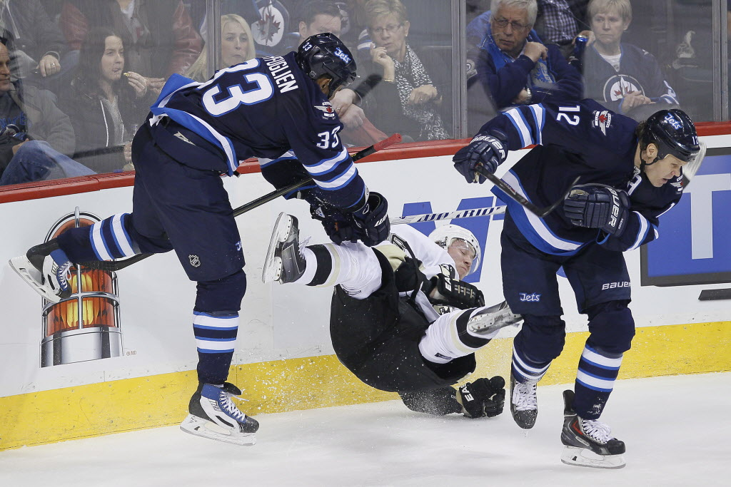 Winnipeg Jets' Dustin Byfuglien (33) takes out Pittsburgh Penguins' Jussi Jokinen (36) with a check as Jets' Olli Jokinen (12) avoids a hit during the first period.