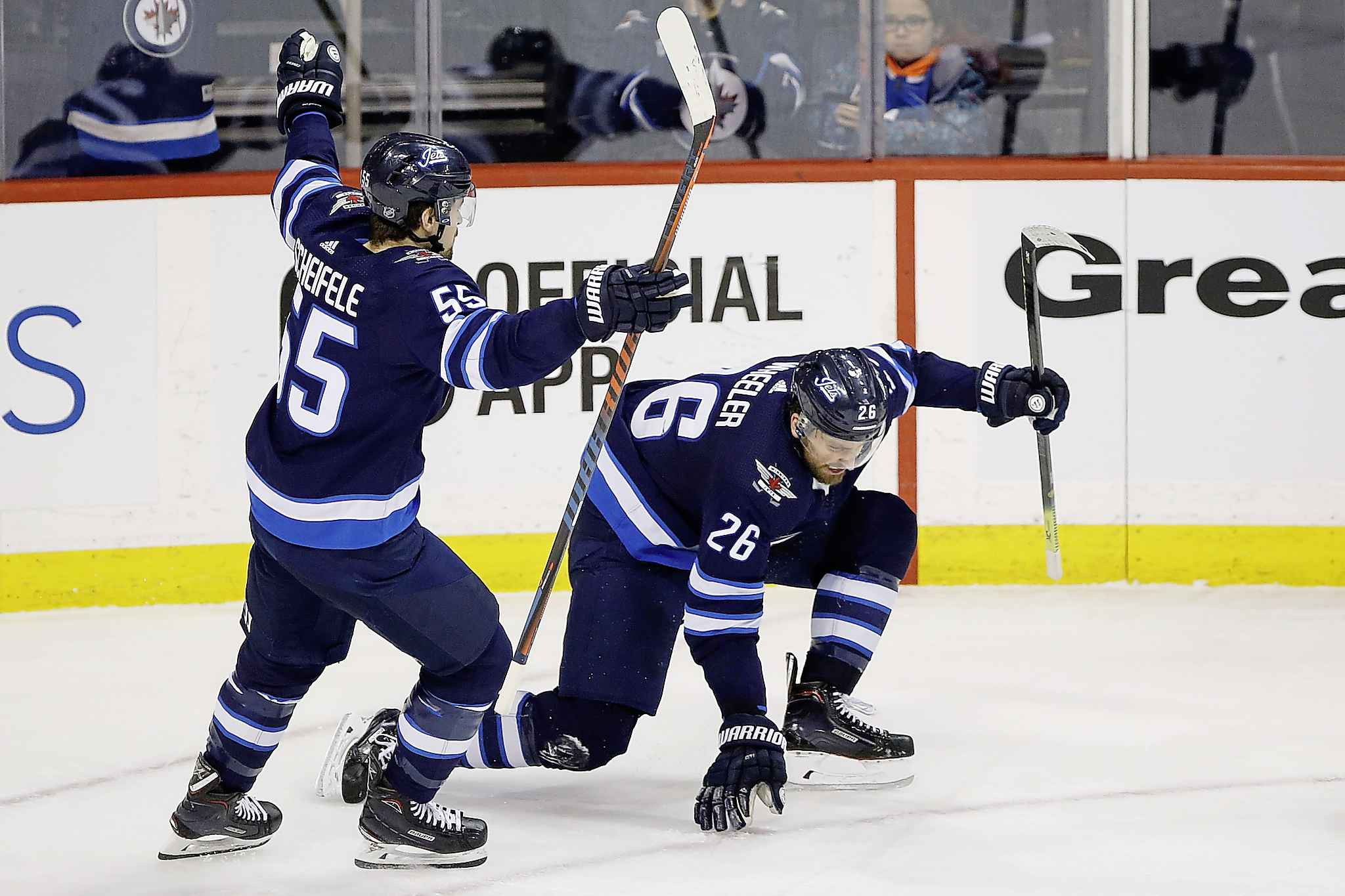 Blake Wheeler (right) and Mark Scheifele celebrate Wheeler's go-ahead goal at 14:09 of the third period. (John Woods / The Canadian Press)