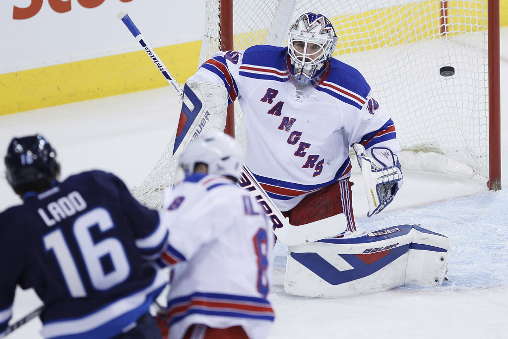 Winnipeg Jets' Andrew Ladd (16) scores on New York Rangers' goaltender Henrik Lundqvist (30) and Kevin Klein (8) during the first period.