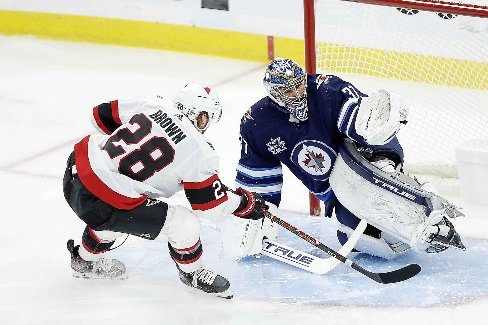 Winnipeg Jets goaltender Connor Hellebuyck (37) saves the shot by Ottawa Senators' Connor Brown (28) during first period NHL action in Winnipeg on Saturday, January 23, 2021. (John Woods / The Canadian Press)