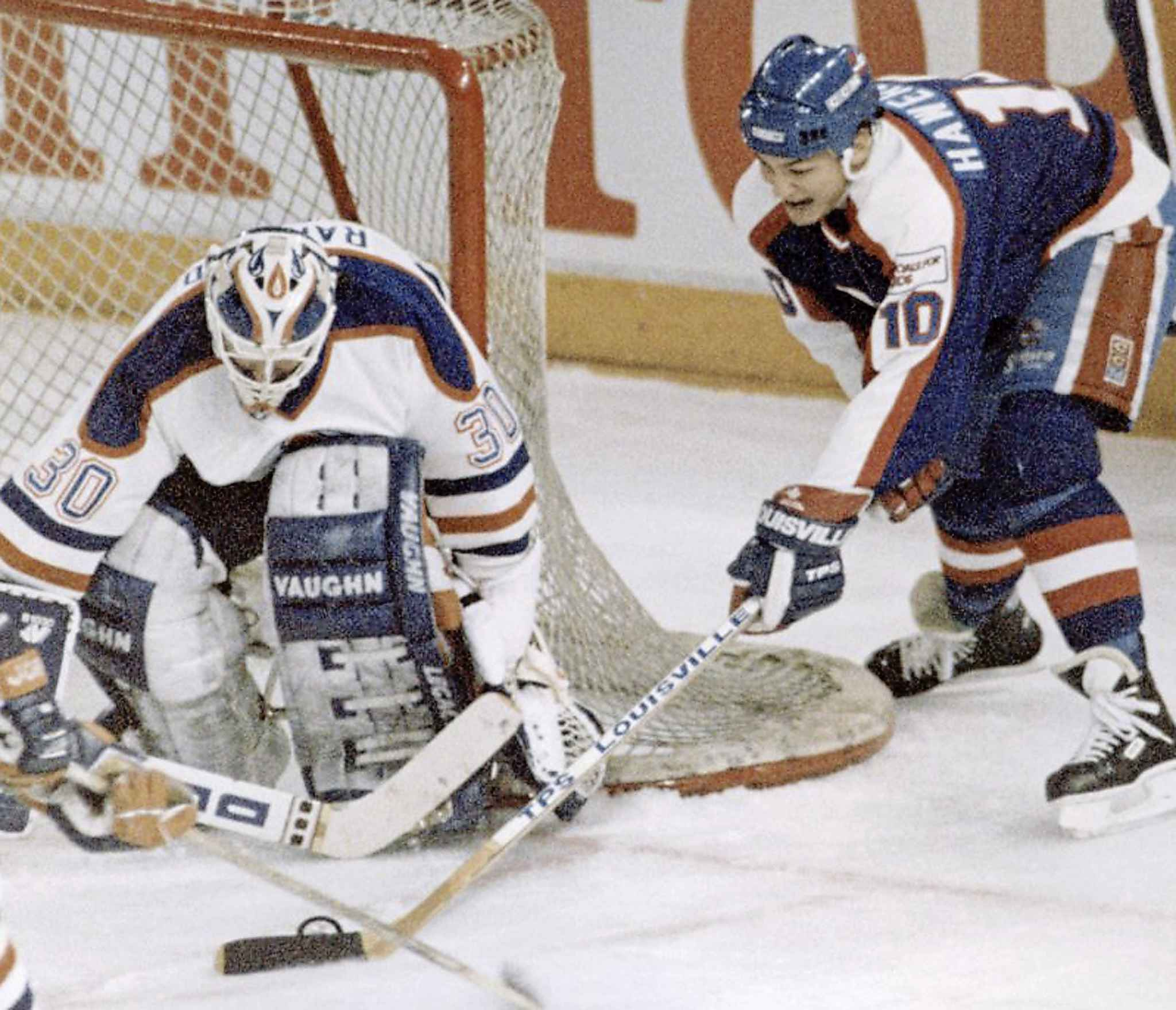 Hawerchuk tries to get the puck past Bill Ranford during a playoff game in Edmonton on April 4, 1990. (Ray Giguere / The Canadian Press files)