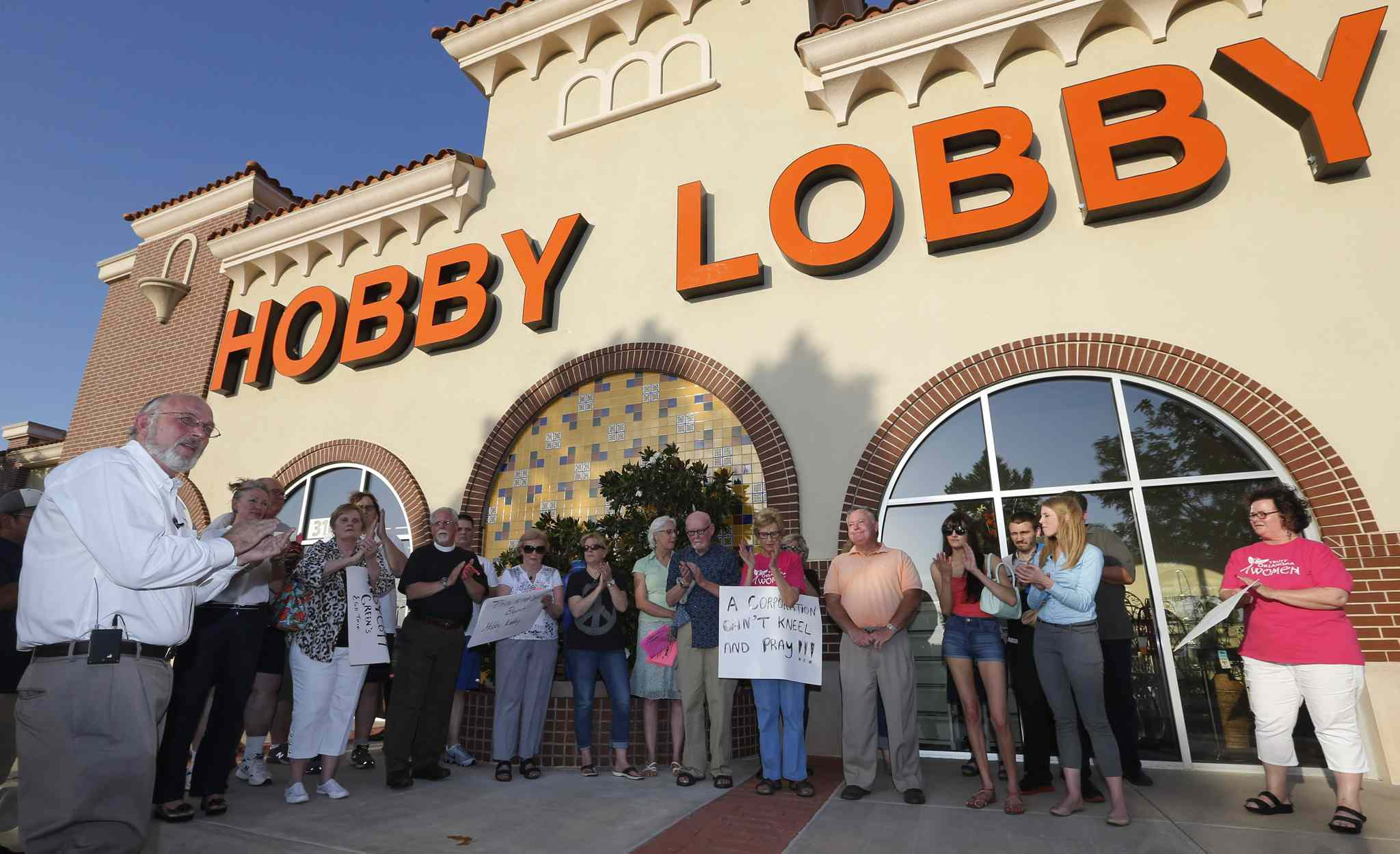 Rev. Bruce Prescott, left, applauds during a vigil outside a Hobby Lobby store in Edmond, Okla., Monday, June 30, 2014, in reaction to the Supreme Court's decision that some companies like the Oklahoma-based Hobby Lobby chain of arts-and-craft stores can avoid the contraceptives requirement in President Barack Obama's health care overhaul, if they have religious objections.
