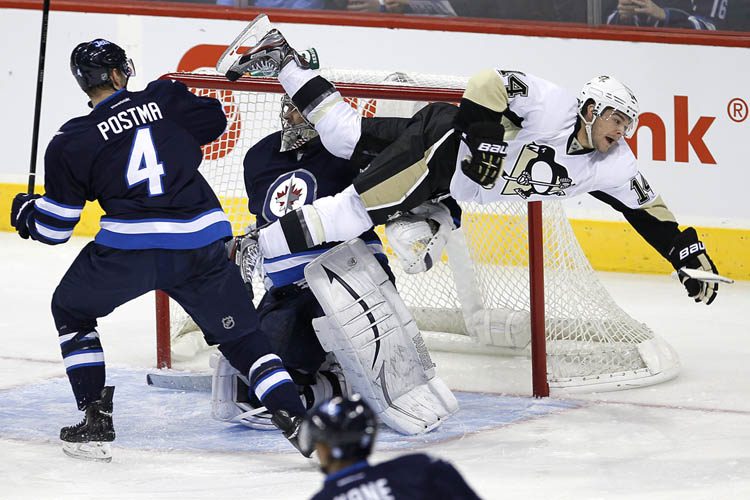 Winnipeg Jets' Paul Postma, 4, sends Pittsburgh Penguins' Chris Kunitz, 14, flying in front of Jets goaltender Ondrej Pavelec during the first period in Winnipeg Friday night. (John Woods / The Canadian Press)