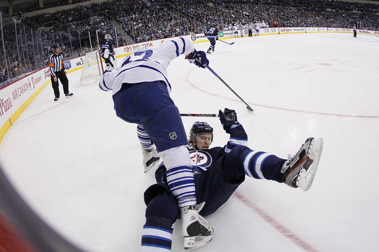 Winnipeg Jets' Bryan Little and Toronto Maple Leafs' Leo Komarov get tangled up in the Jets zone during the second period at MTS Centre Thursday night. (JOHN WOODS / The Canadian Press)