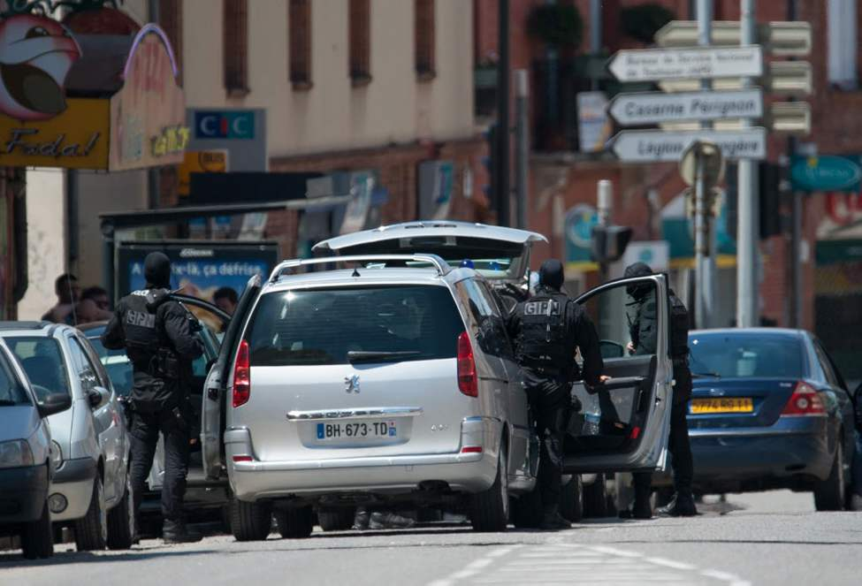 Elite police officers from the GIPN brigade arrive at the bank, seen behind at left with CIC sign, where a man took hostages in the southern French city of Toulouse and fired a shot, police said. French television reported that he claimed allegiance to the al-Qaida terrorist group.(AP Photo/Bruno Martin)