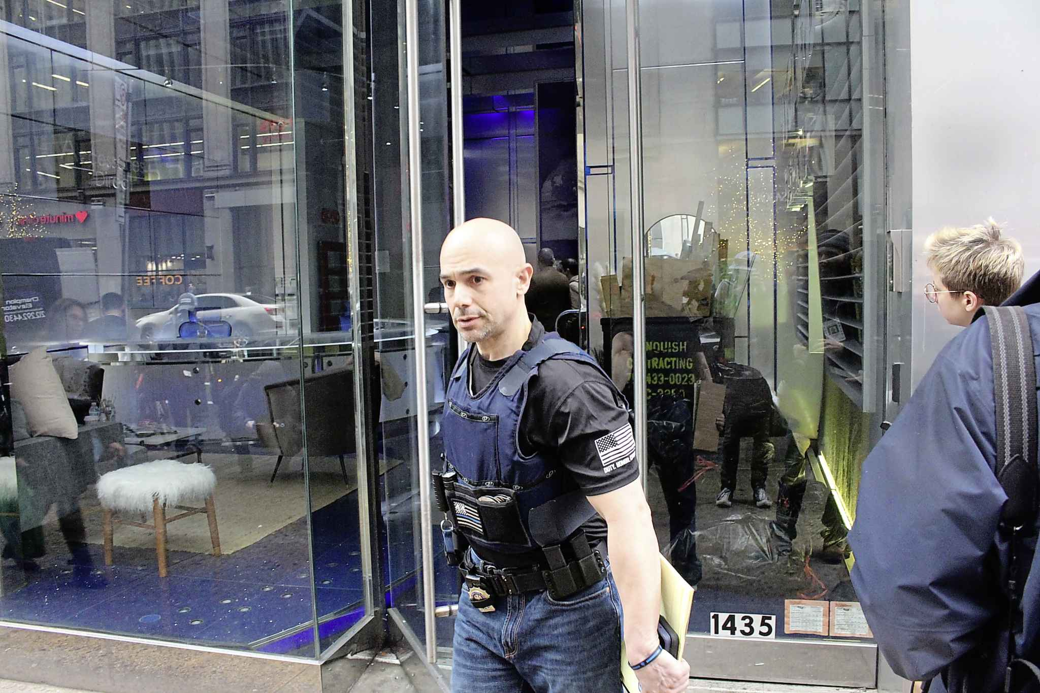 A law enforcement officer exits Nygard's headquarters in Times Square in New York. (Ryan Thorpe / Winnipeg Free Press)