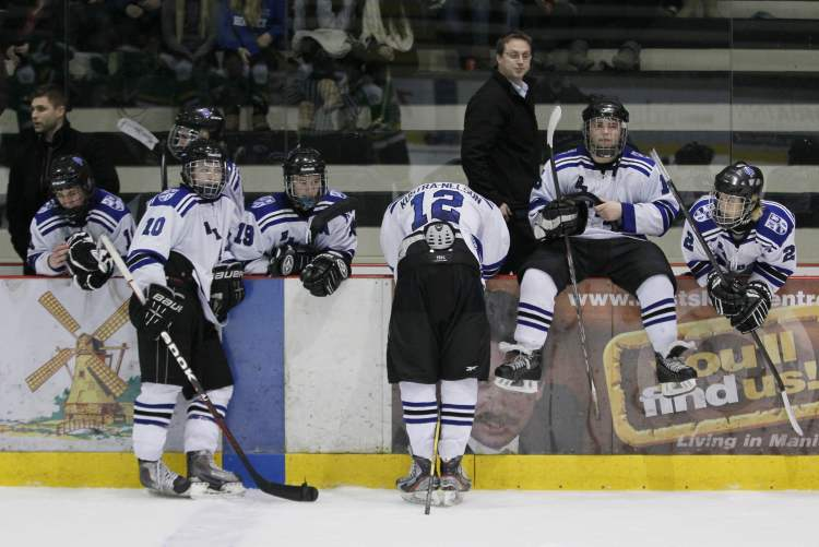 A dejected Oak Park Raiders team gathers at the bench after being defeated by the John Taylor Pipers in the Winnipeg High School Hockey League Final at MTS Iceplex Tuesday February 26, 2013.  John Woods / Winnipeg Free Press