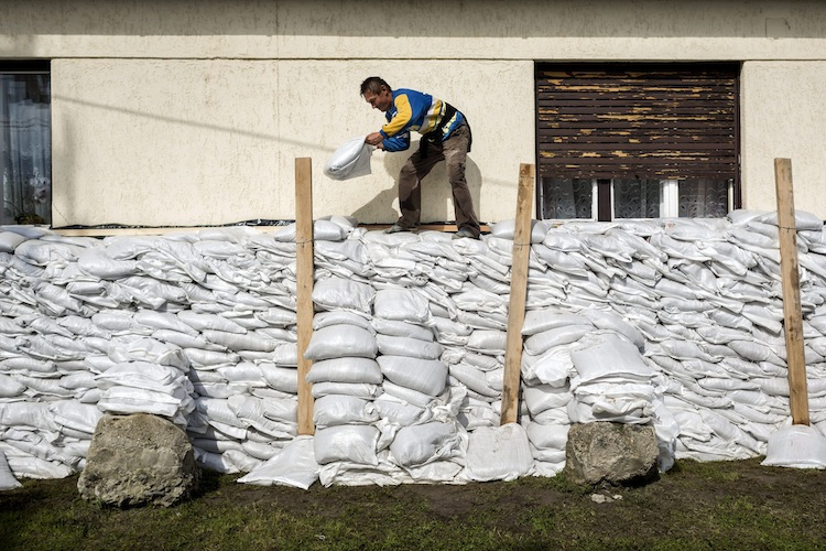 A man protects his house with sandbags in Tahitotfalu, about 30 kilometres north of Budapest, Hungary. (Balazs Mohai / The Associated Press)