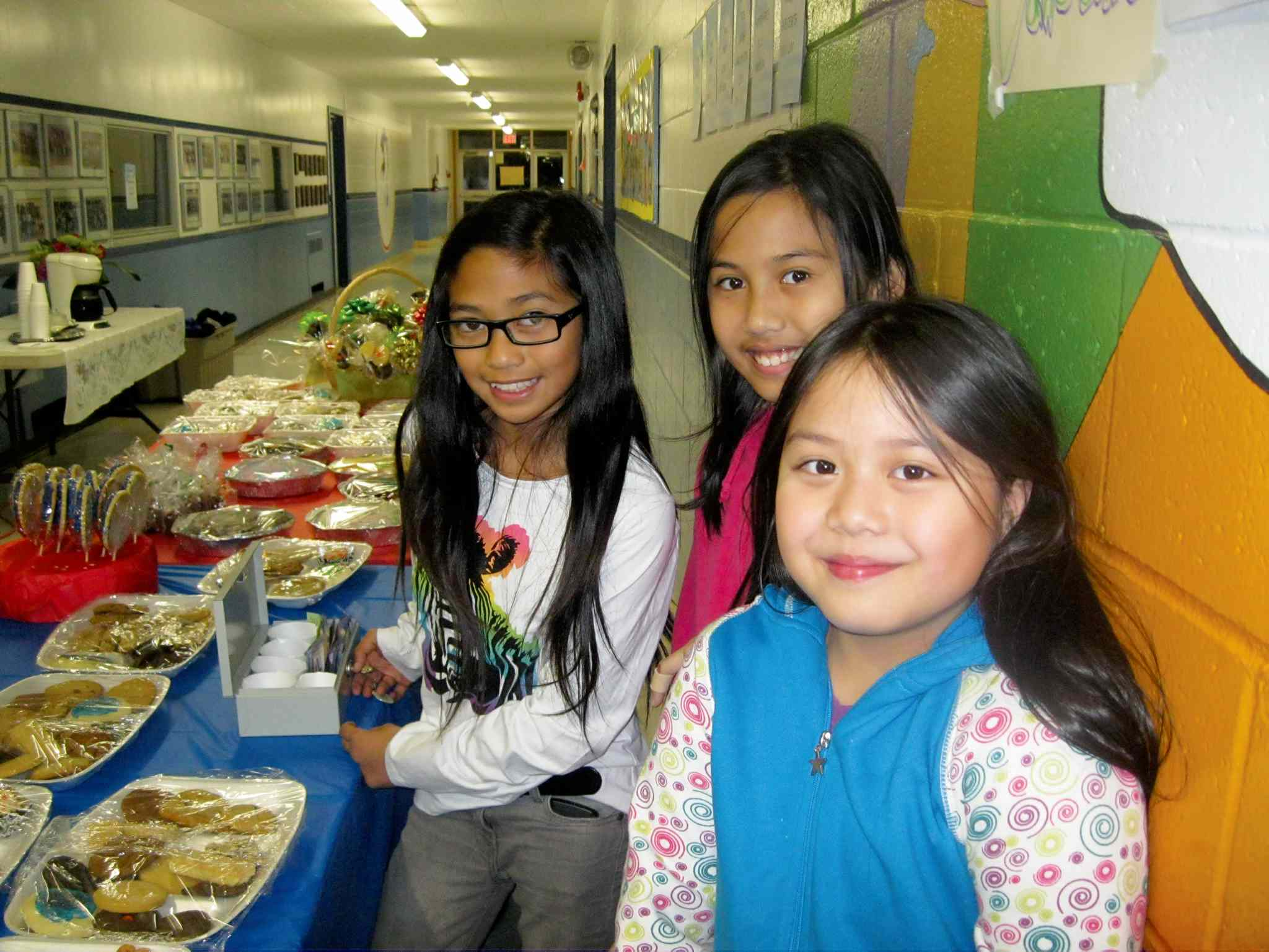 Kent Road School students Sydney Decanay, Samantha Aguila and Hannah Ang are shown creating posters for the school's bake sale in support of Filipino relief.