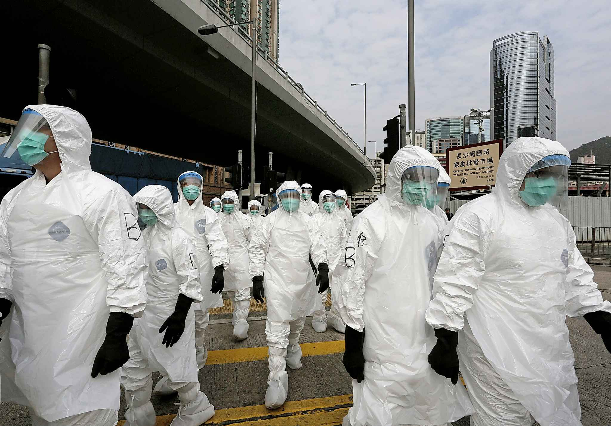 Health workers in full protective gear walk at a wholesale poultry market before culling the poultry in Hong Kong in 2014. Hong Kong authorities culled 20,000 birds at a wholesale market after poultry from southern mainland China tested positive for the H7N9 virus.