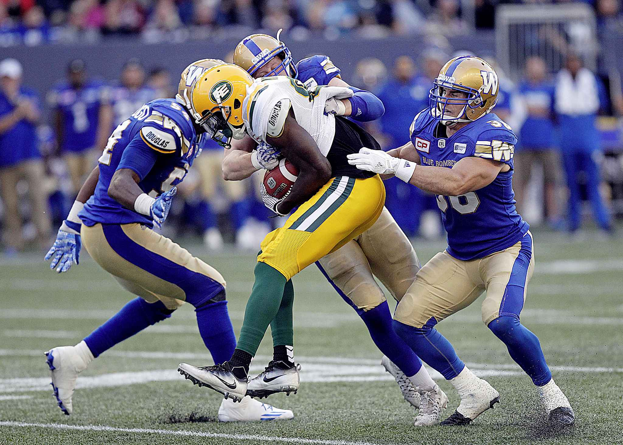 Edmonton Eskimos' Bryant Mitchell is gang tackled by, from left to right, Winnipeg Blue Bombers' Tristan Okpalaugo, Sam Hurl and Ian Wild Thursday evening at Investors Group Field.