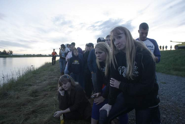 Jeane Ebeling (from right) and Allee McCoy of Mount Vernon look at the collapsed bridge in the Skagit River.