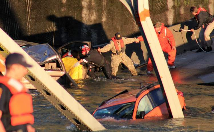 Rescue workers form a human chain to remove a woman from a smashed pickup truck that fell into the Skagit River. (Francisco Rodriguez / The Associated Press)