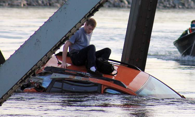 A man is seen sitting atop a car that fell into the Skagit River after the collapse of the Interstate 5 bridge there minutes earlier.
