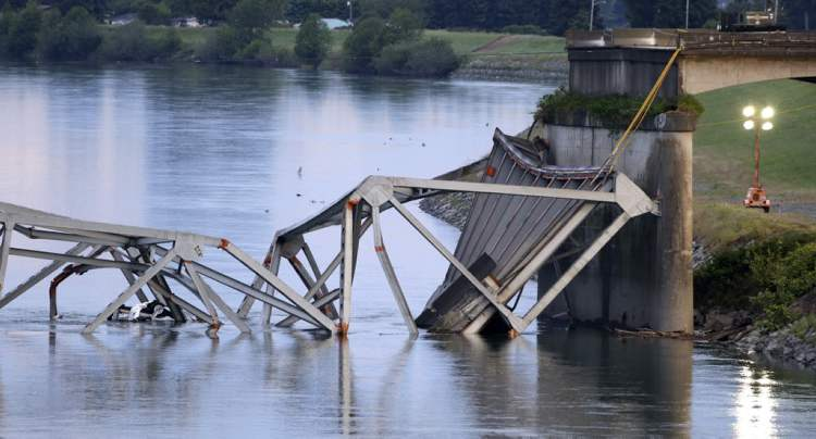 A collapsed portion of the Interstate 5 bridge lies at the Skagit River. At an overnight news conference, Washington State Patrol Chief John Batiste blamed the collapse on a tractor-trailer carrying a tall load that hit an upper part of the span.