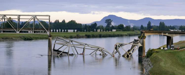 A collapsed portion of the Interstate 5 bridge lies in the Skagit River Friday, May 24, 2013, in Mount Vernon, Wash. (Elaine Thompson / The Associated Press)