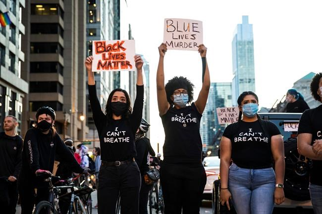 Protesters holds placards Saturday afternoon, May 30, 2020 in Chicago, I.L., as they join national outrage over the death of George Floyd, who died in police custody on Memorial Day in Minneapolis.(Ashlee Rezin Garcia/Chicago Sun-Times via AP)