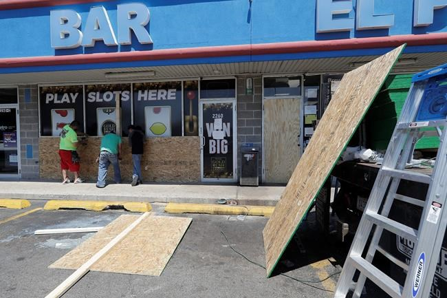 Workers board up windows at a store Tuesday, June 2, 2020, in Chicago. Chicago's Cicero neighborhood was vandalized last Monday in protests over the death of George Lloyd, a black man who died while in police custody on May 25. (AP Photo/Nam Y. Huh)