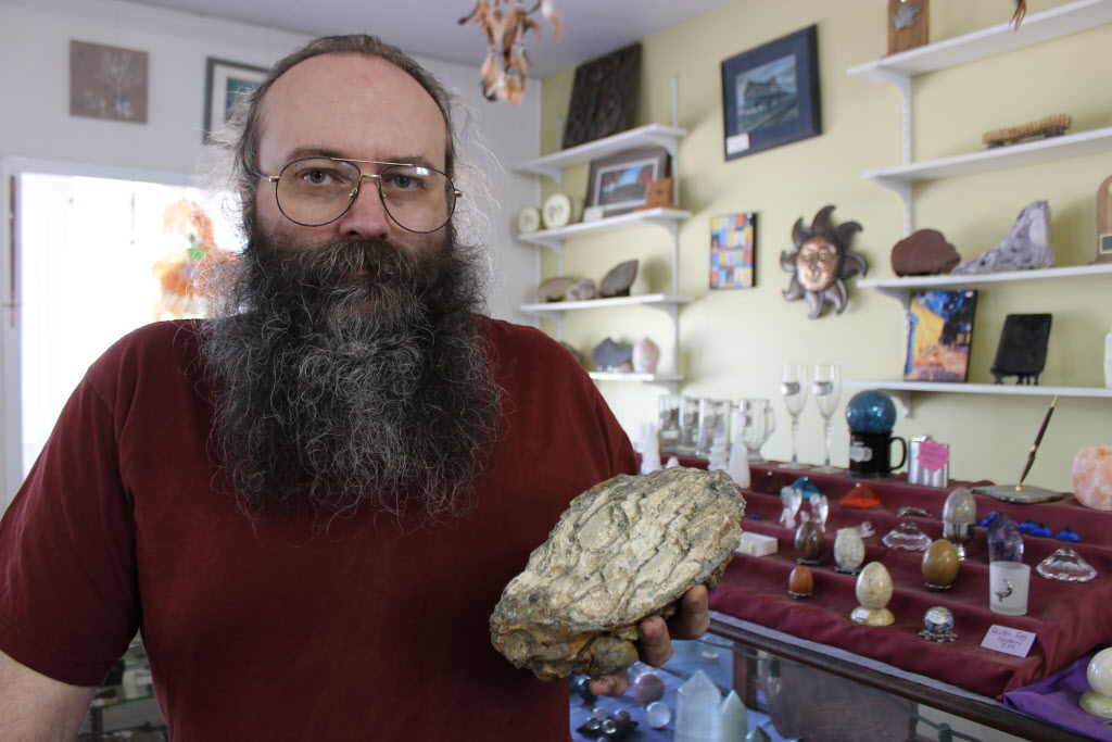Souris Rock Shop owner Frank Grabowski holds up a fossilized mammoth tooth he found last year in the store's quarry.