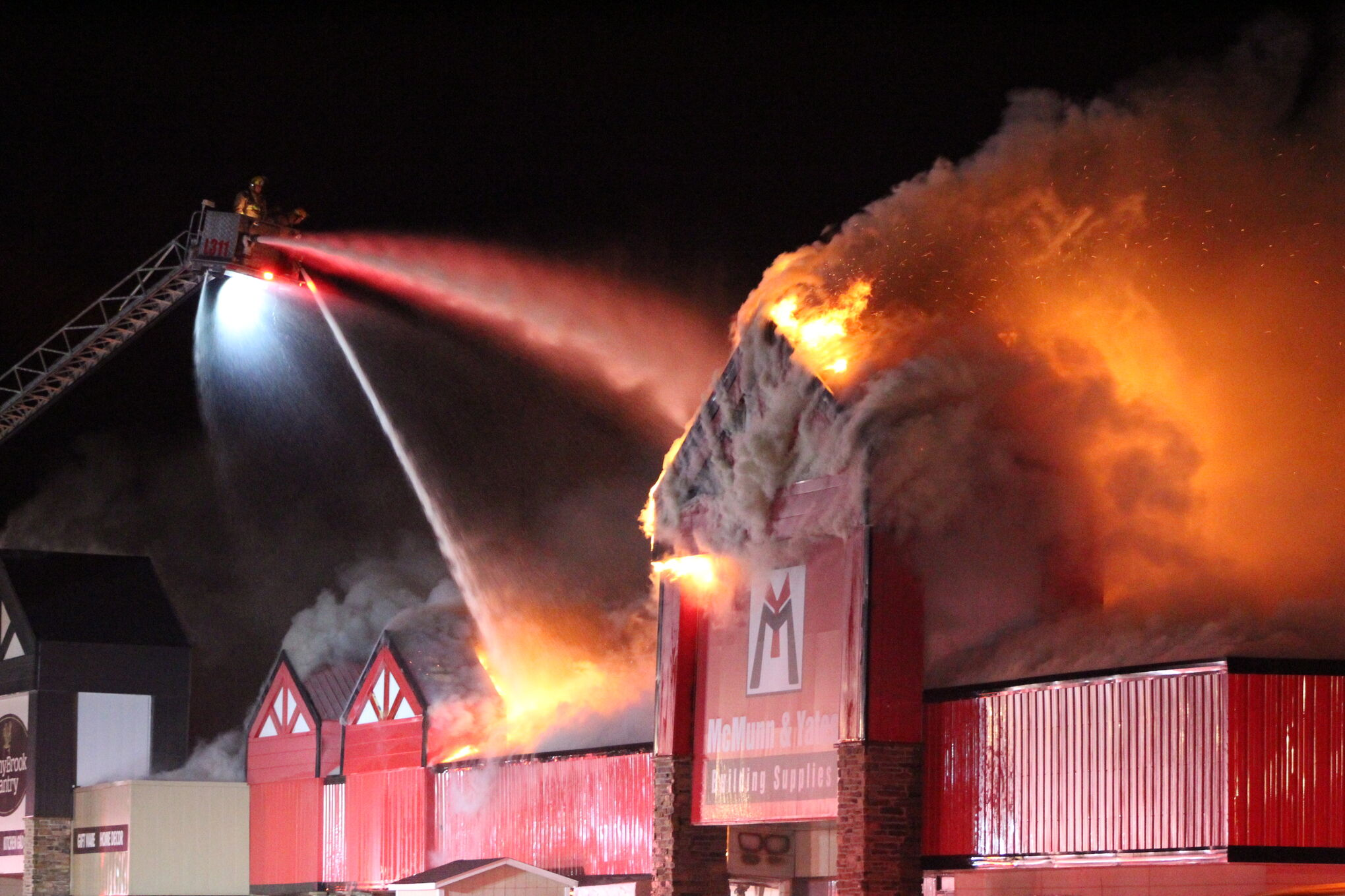 Firefighters douse flames from atop an aerial ladder.