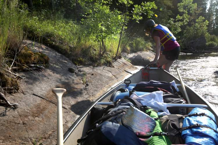 The paddling duo walked their canoe along the edge of a set of fast-moving rapids to avoid getting dunked. (Ruth Bonneville / Winnipeg Free Press)