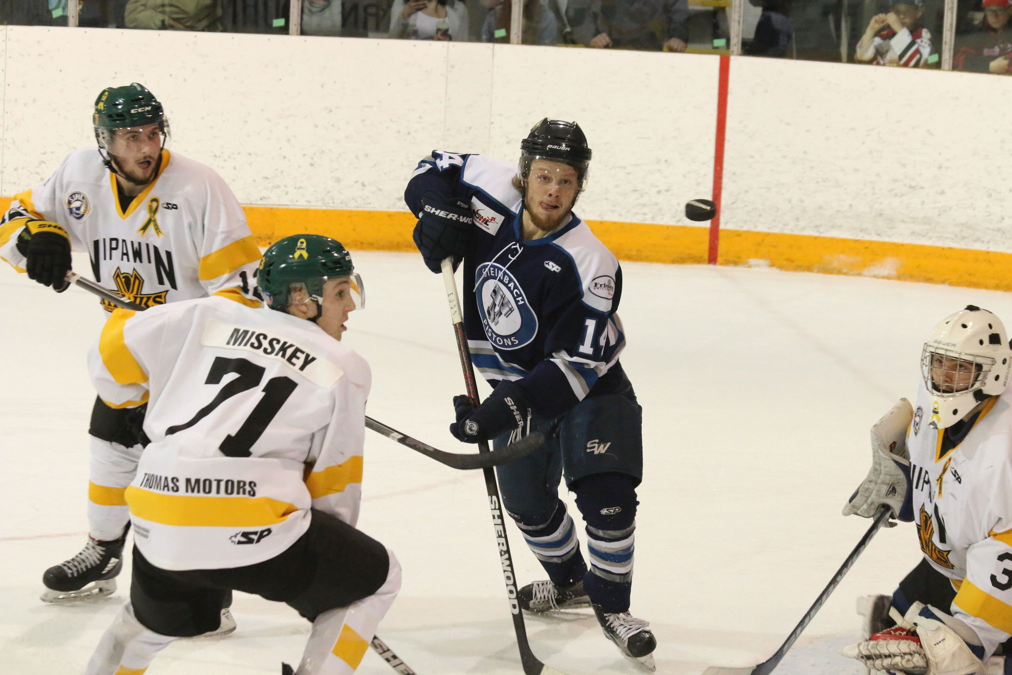 Pistons' forward Jack Johnson keeps an eye on an airborne puck in front of goaltender Declan Hobbs Tuesday night in Nipawin as the Steinbach Pistons crushed the hometown Hawks 6-2 to take a 2-1 ANAVET Cup series lead.
