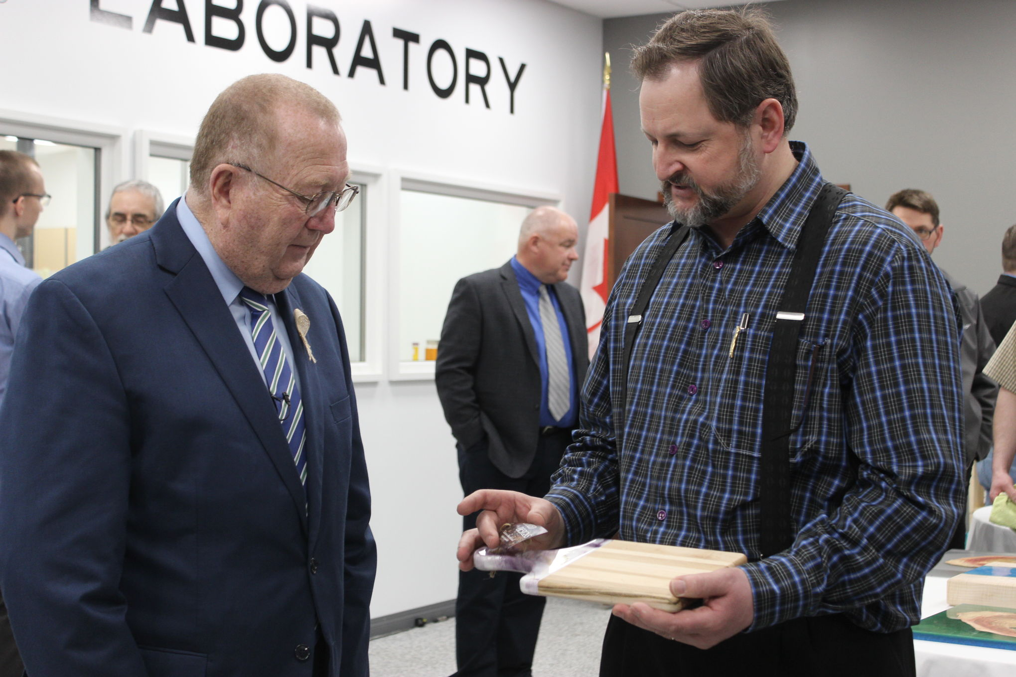 EcoPoxy CEO Jack Maendel presents Agriculture Minister Ralph Eichler with an epoxy-accented wooden cutting board made by Mike Cancade, executive assistant to Provencher MP Ted Falk. Maendel says his company, located near Morris, will use $167,000 in joint government funding to purchase much-needed packaging and testing equipment.