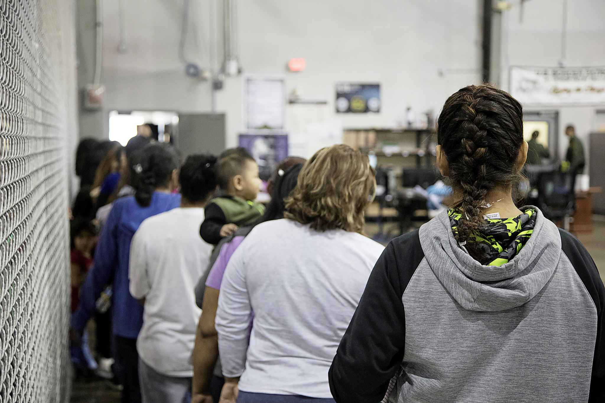 In this photo provided by U.S. Customs and Border Protection, people who've been taken into custody related to cases of illegal entry into the United States, stand in line at a facility in McAllen, Texas, Sunday, June 17, 2018. (U.S. Customs and Border Protection's Rio Grande Valley Sector / The Associated Press)