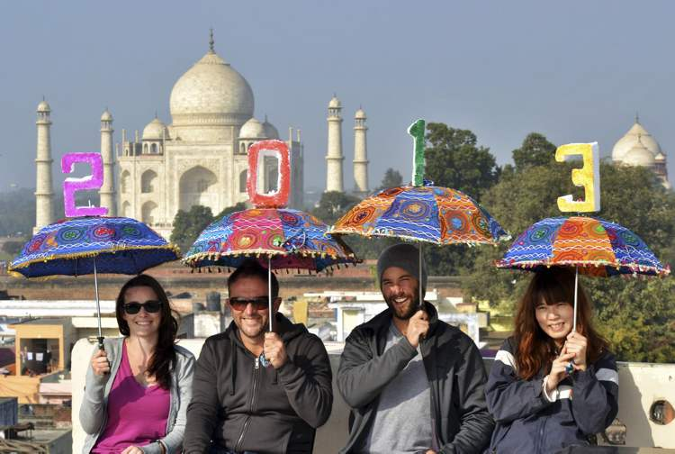 Tourists pose as they carry umbrellas with numbers to welcome 2013 on the terrace of a hotel in the backdrop of Taj Mahal in Agra, India.