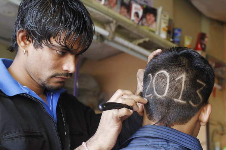 An Indian barber gives finishing touches to the hair style of a young boy with numbers to welcome the New Year 2013 in Ahmadabad, India.