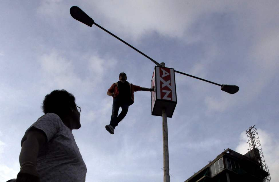 A passer-by watches as magicians and illusionists Cyril Takayama performs on a roadside electric pole , in Mumbai, India, Friday, June 15, 2012. Takayama is in India to promote his television show.