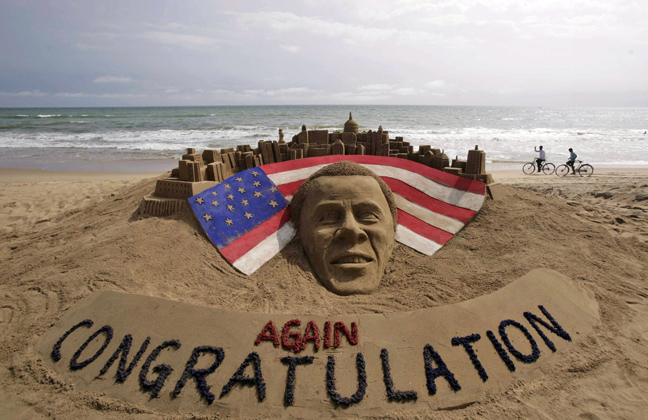 Cyclists ride on a beach passing by a sand sculpture congratulating U.S. president Barack Obama for a second term in office in Puri, India, Wednesday. Obama captured a second White House term, blunting a mighty challenge by Republican Mitt Romney as Americans voted for a leader they knew over a wealthy businessman they did not.