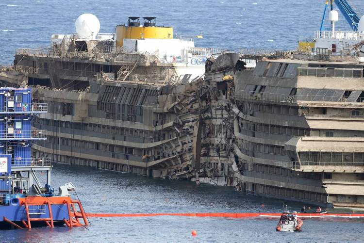 """The Costa Concordia is seen after it was lifted upright, on the Tuscan Island of Giglio, Italy, Tuesday, Sept. 17, 2013. The crippled cruise ship was pulled completely upright early Tuesday after a complicated, 19-hour operation to wrench it from its side where it capsized last year off Tuscany, with officials declaring it a """"perfect"""" end to a daring and unprecedented engineering feat.  (Andrea Sinibaldi / The Associated Press)"""