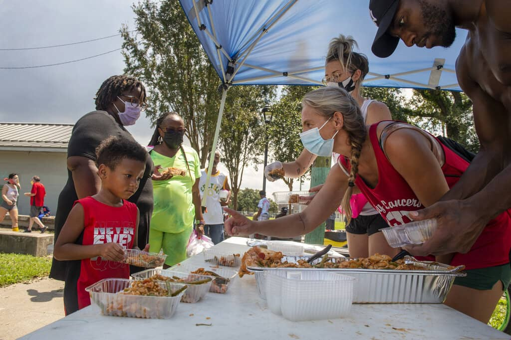 Volunteers and neighbors with the Committee for a Better New Orleans serve food in the St. Roch neighborhood of New Orleans on Tuesday. (Chris Granger / The Times-Picayune/The New Orleans Advocate)