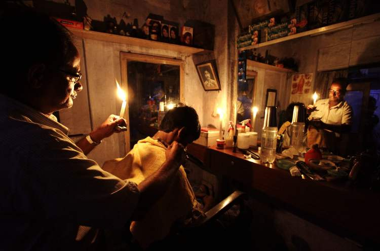 An Indian barber, holding a candle, gives a customer a haircut at his shop in Kolkata, India, Tuesday, July 31, 2012. India's energy crisis cascaded over half the country Tuesday when three of its regional grids collapsed, leaving 620 million people without government-supplied electricity for several hours in one of the world's biggest-ever blackouts. (AP Photo/Bikas Das)