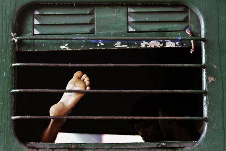 A stranded Indian train passenger rests inside a railway coach as he waits for the train service to resume following a power outage in Kolkata, India, Tuesday, July 31, 2012. India's energy crisis cascaded over half the country Tuesday when three of its regional grids collapsed, leaving 620 million people without government-supplied electricity for several hours in one of the world's biggest-ever blackouts. (AP Photo/Bikas Das) (CP)
