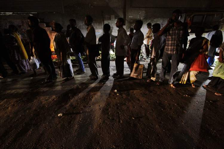 Indian commuters wait for a bus on a street illuminated with street vendor's kiosks following a power outage in Kolkata, India, Tuesday, July 31, 2012. India's energy crisis cascaded over half the country Tuesday when three of its regional grids collapsed, leaving 620 million people without government-supplied electricity for several hours.  (AP Photo/Bikas Das) (CP)