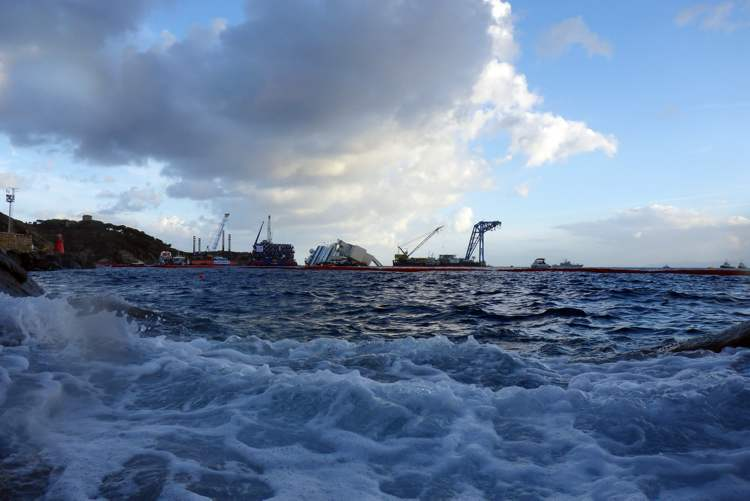 The Costa Concordia ship lies on its side on the Tuscan Island of Giglio, Italy, early Monday morning, Sept. 16, 2013. An international team of engineers is trying a never-before attempted strategy to set upright the luxury liner, which capsized after striking a reef in 2012 killing 32 people. (AP Photo/Andrew Medichini) (CP)