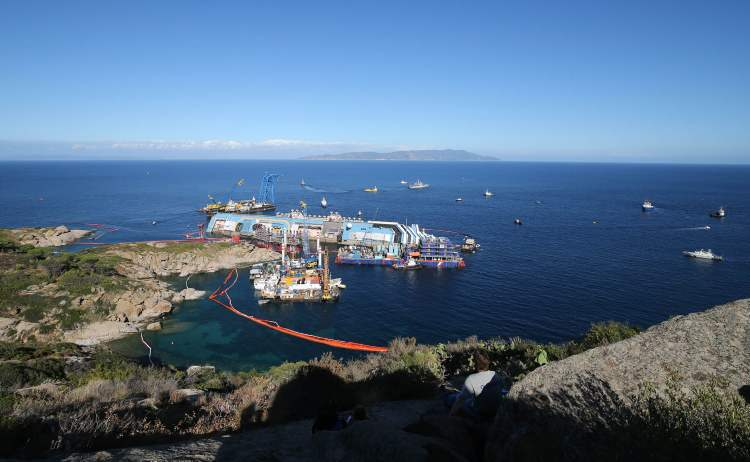 The Costa Concordia ship lies on its side on the Tuscan Island of Giglio, Italy, Monday, Sept. 16, 2013. Engineers on Monday succeeded in wresting the hull of the shipwrecked Costa Concordia from the Italian reef where it has been stuck since it capsized in January 2012, leaving them cautiously optimistic they can rotate the luxury liner upright and eventually tow it away. Never before has such an enormous cruise ship been righted, and the crippled Concordia didn't budge for the first three hours after the operation began, engineer Sergio Girotto told reporters. (AP Photo/Andrea Sinibaldi, Lapresse) (CP)