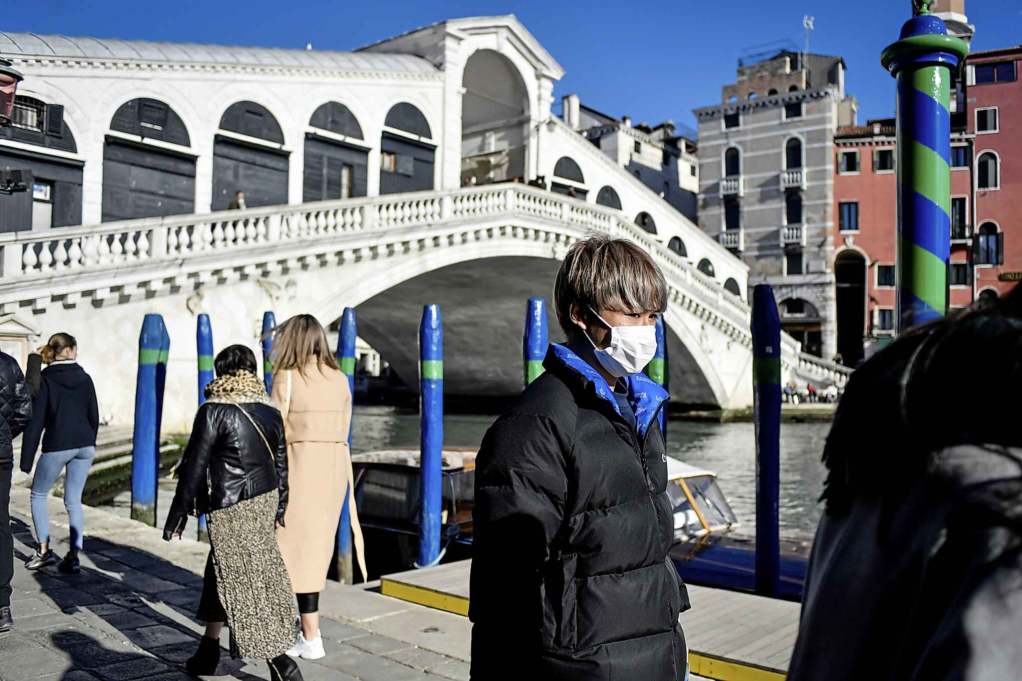 A man wearing a protective mask walks past the Rialto Bridge in Venice, Italy on Friday. The number of countries in which COVID-19 has been confirmed approached 60 by the end of the week. (Claudio Furlan / Lapresse)