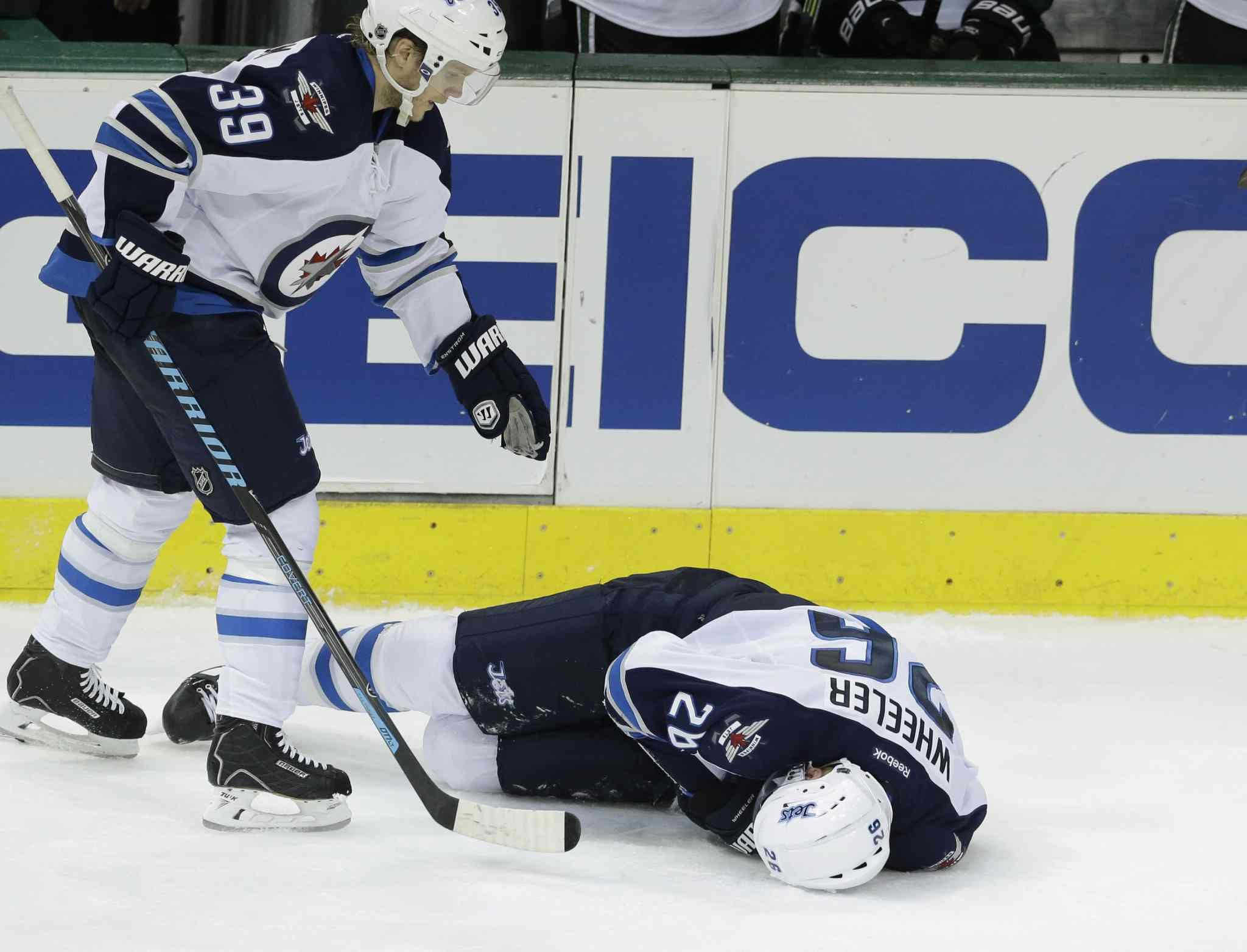 Winnipeg Jets defenceman Tobias Enstrom skates over to check on teammate Blake Wheeler after Wheeler was knocked into an open gate at the Stars' bench in the third period. Wheeler was injured on the play but returned for a shift late in the game.