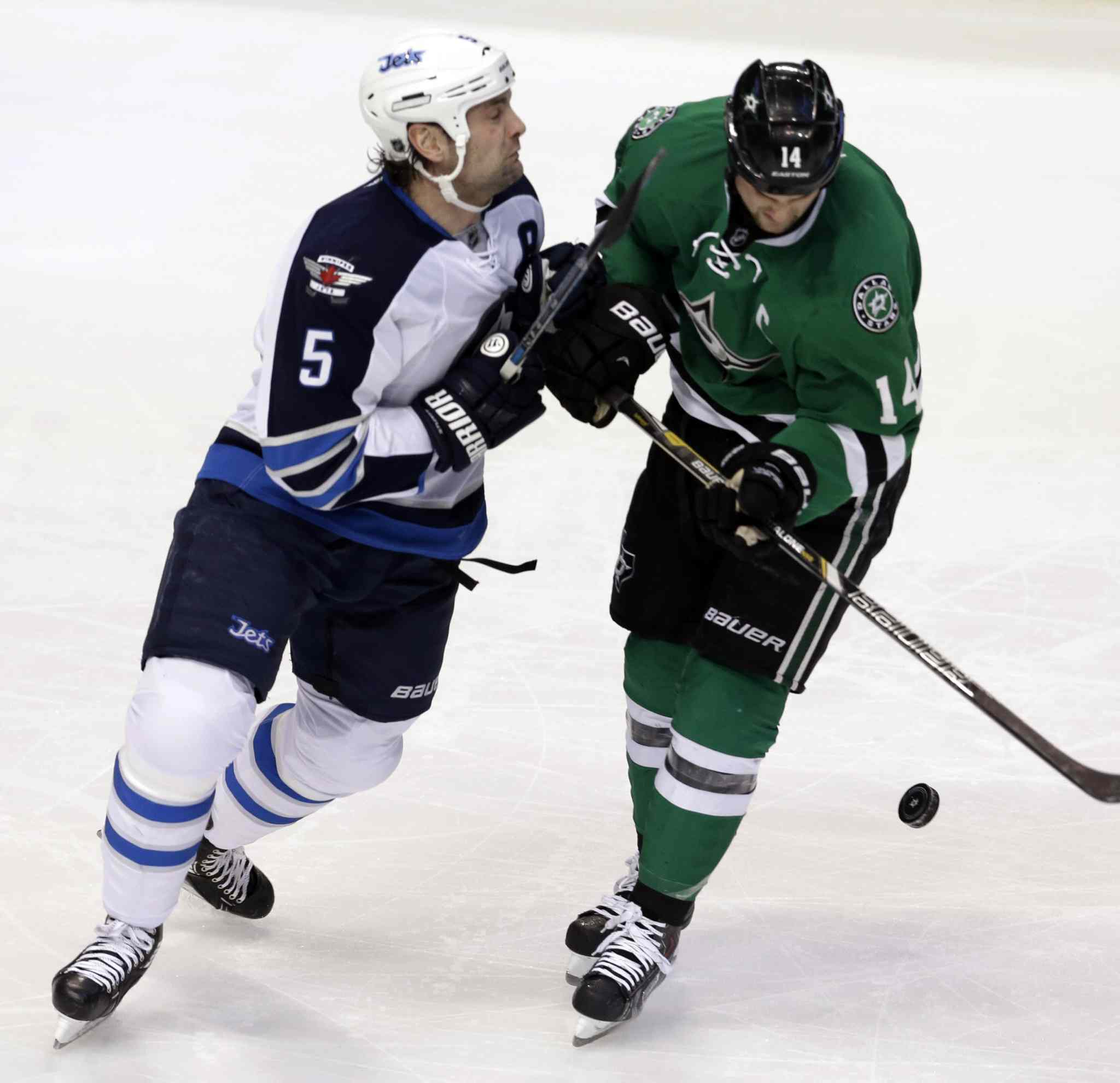 Winnipeg Jets defenceman Mark Stuart and Dallas Stars left-winger Jamie Benn battle for the puck during the first period.