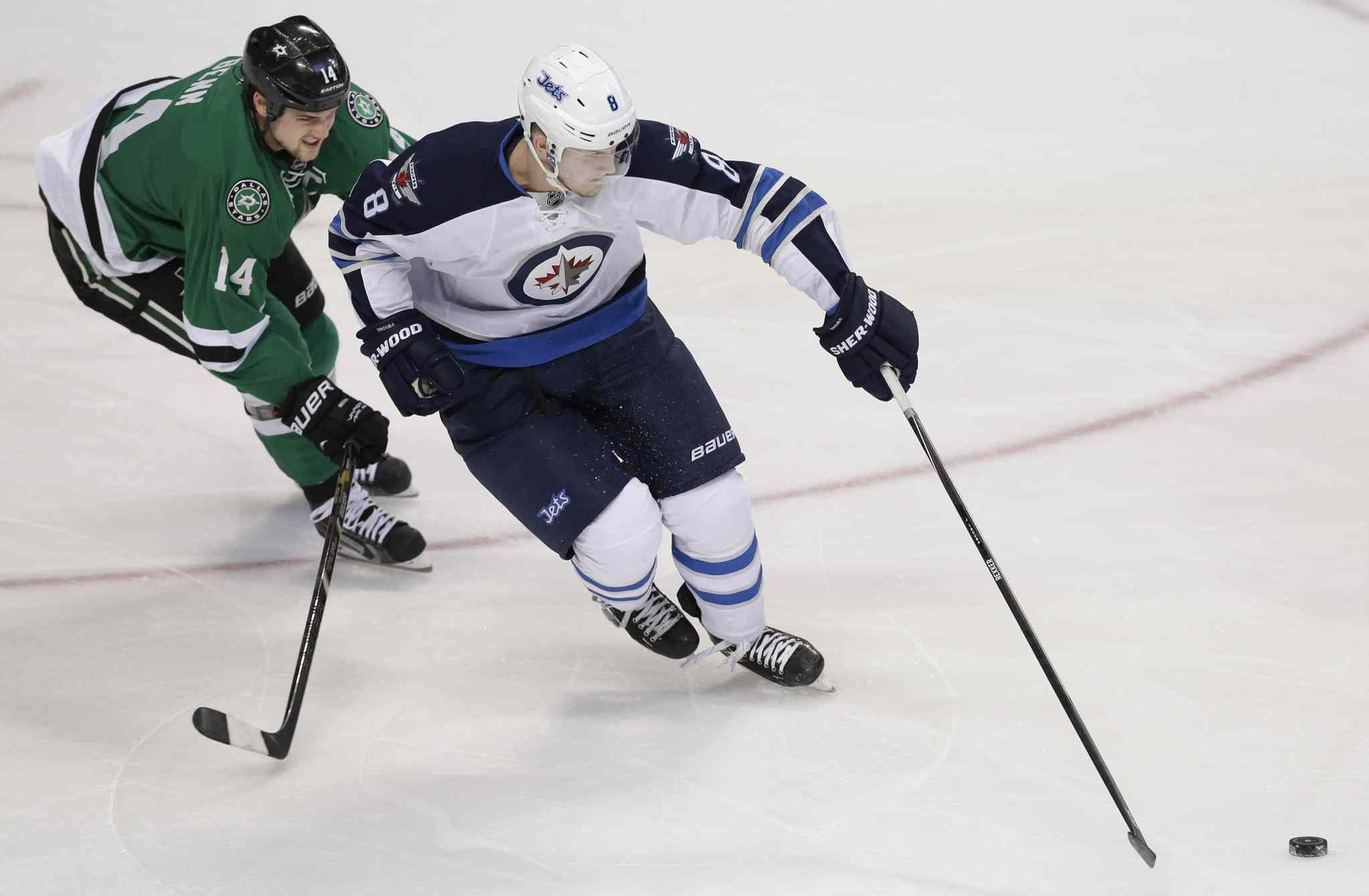 Winnipeg Jets defenceman Jacob Trouba skates with the puck while being pursued by Dallas Stars left-winger Jamie Benn during the first period of an NHL game at American Airlines Arena in Dallas Monday.