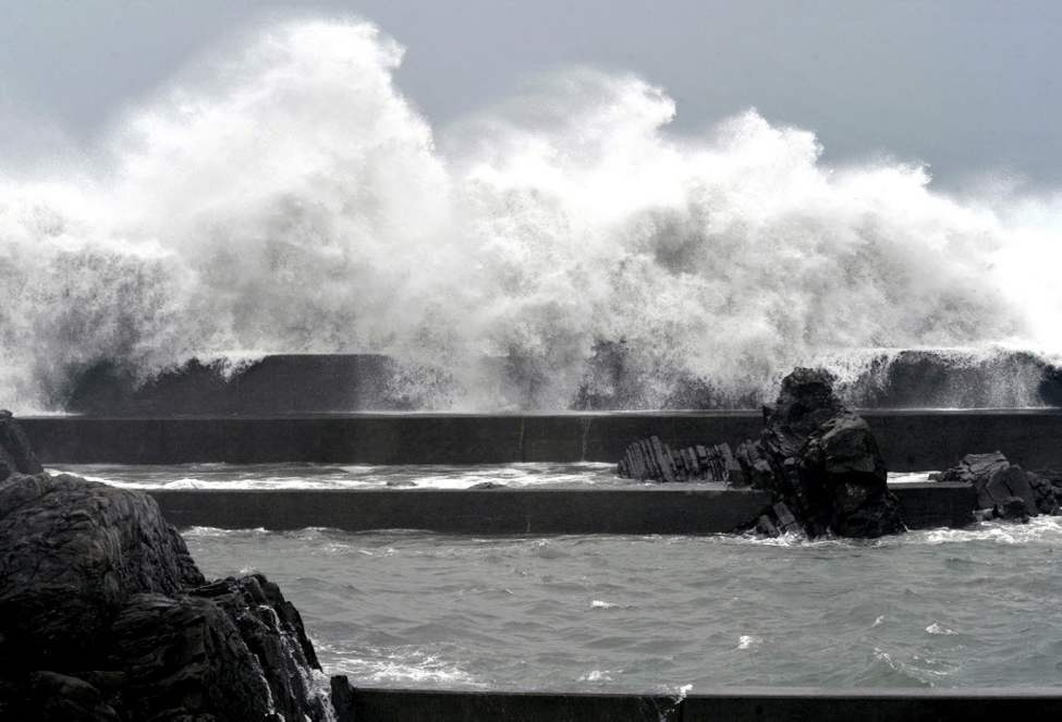 A high wave hits a pier at a fishing port in Muroto, Kochi Prefecture, Japan. Typhoon Guchol continued moving across northern Honshu toward Hokkaido, bringing heavy rain and strong winds before it turns northwest and into the Pacific Ocean. (AP Photo/Kochi Shimbun via Kyodo News)