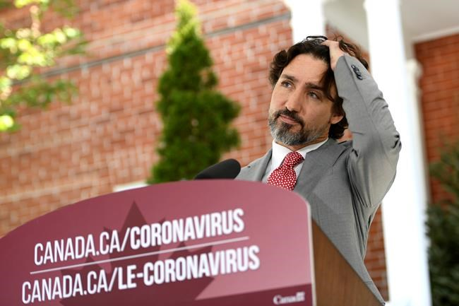 Prime Minister Justin Trudeau brushes his hair out of his eyes as he listens to a question during his daily news conference on the COVID-19 pandemic outside his residence at Rideau Cottage in Ottawa, on Wednesday, May 20, 2020. THE CANADIAN PRESS/Justin Tang